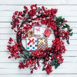 Holly christmas wreath with gift boxes on wooden table. — Stock Photo #59319371