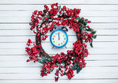 Holly christmas wreath with clock on wooden table. — Stock Photo