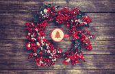 Holly christmas wreath on wooden table. — Stock Photo