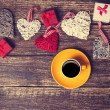 Cup of coffee near heart shape toys on a wooden table. — Stock Photo #59464697