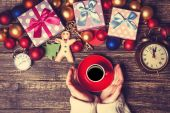 Female holding cup of coffee near christmas gifts on a table — Stock Photo