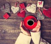 Female holding cup of coffee near heart shape toys on a table. — Stock Photo