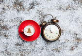Cappuccino with christmas tree shape and clock on artificial bac — Stock Photo