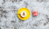 Cappuccino with christmas tree shape and gift box on artificial — Stock Photo