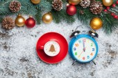 Cappuccino with christmas tree shape and clock on artificial sno — Stock Photo