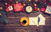 Hot coffee with letter near christmas gifts on wooden table. — Stock Photo