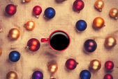 Hot coffee and christmas balls on jute background.  — Stock Photo
