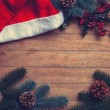Santas hat and pine branch on wooden table. — Stock Photo #59938157