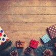 Christmas gifts near pine branch on wooden table. — Stock Photo #59938373