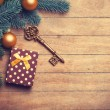 Christmas tree branch with toy balls and gift on wooden table. — Stock Photo #59938595