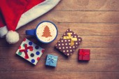 Cappuccino with christmas hat and gift on wooden table. — Stock Photo