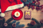 Cup of coffee and gift box with pine and hat on wooden table. — Stock fotografie