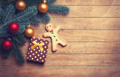 Gingerbread man and gift on wooden table. — Stock Photo