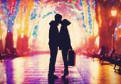 Couple with suitcase kissing at night alley. — Stock Photo