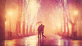 Couple with umbrella kissing at night alley. — Stock Photo