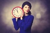 Women in blue dress with huge clock  — Stockfoto