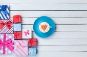 Cup of Cappuccino and gift boxes — Stock Photo