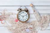 Alarm clock and net with shells and bottle  — Stock Photo