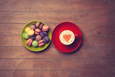 Cup and macarons on wooden background — Stock Photo
