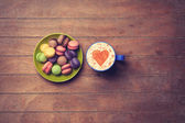 Cup and macarons on wooden background — Stockfoto
