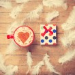 Coffee and feathers with gift on wooden background. — Stock Photo #64908677