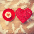 Toy heart and cup of coffee with heart shape and feathers — Stock Photo #64908741