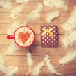 Coffee and feathers with gift on wooden background. — Stock Photo #64908611