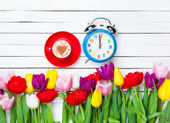 Cappuccino and clock near flowers — Stock Photo