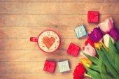 Cappuccino and gifts near flowers — Stock Photo