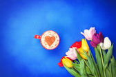Cup near flowers on blue background — Stock Photo