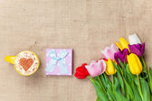 Cappuccino and gift box near flowers  — Stock Photo