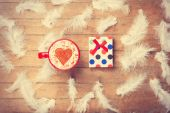 Coffee and feathers with gift on wooden background. — Stock Photo