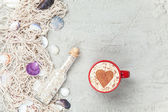 Cup, bottle and net with shells on sand — Stock Photo