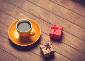 Cup of coffee and gift boxes on a wooden table. — Foto de Stock