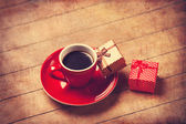 Cup of coffee and gift box on a wooden table. — Stock Photo