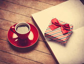 Cup of coffee and gift box with book on a wooden table — Stock Photo
