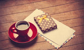 Cup of coffee and gift box with envelopes on a wooden table.  — Stock Photo