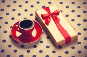 Cup of coffee and gift box on a polka dot background. — Stock Photo