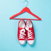 Red gumshoes with white shoelaces and hanger — Stockfoto