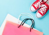 Red gumshoes with shpping bags — Stock Photo