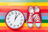 Gumshoes with white shoelaces and clock — Stock Photo