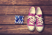 Gumshoes with white shoelaces and gift box — Stock Photo