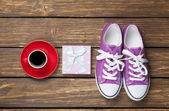 Gumshoes and gift box with coffee cup — Stock Photo
