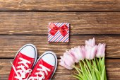 Gumshoes and gift box with tulips — Stock Photo