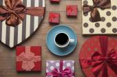 Cup of coffee and gifts around — Stock Photo
