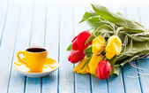 Cup of coffee and bouquet of tulips — Fotografia Stock