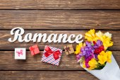 Gift boxes and bouquet of flowers with word Romance — Stock Photo
