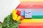 White computer and bouquet of tulips with gift — Stock Photo
