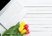 White computer and bouquet of tulips — Stock Photo