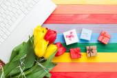 White computer and bouquet of tulips with gifts — Foto Stock
